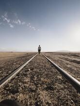 Male Tourist Walking Along Abandoned Straight Railway Train Tracks In Andes Deserted Landscape In Julaca Uyuni Bolivia