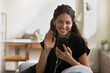 Videocall. Happy millennial latin female in wired pair of headphones sit on couch talk to friend in video app wave hand say hi to caller. Friendly young lady use cell for video call make hello gesture