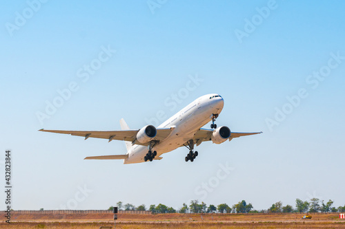 Passenger plane takes off from runway in airport - fototapety na wymiar