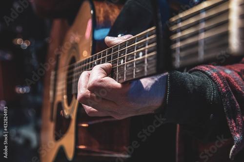 Valokuvatapetti Guitarist playing acoustic guitar in the dark close up.