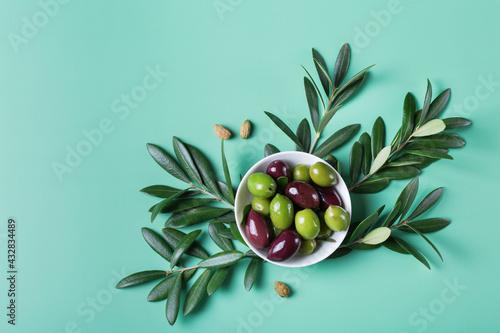 Obraz na plátně Fresh olives and olive tree branch on a table