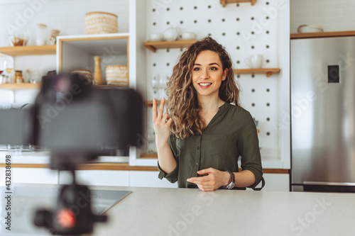 Smiling young woman recording a video at home. - fototapety na wymiar