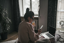 Woman Drinking Coffee While Sitting On Bed