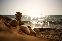 Closeup Of Stacked Pebbles On A Rocky Beach Surrounded By The Sea In Paphos, Cyprus