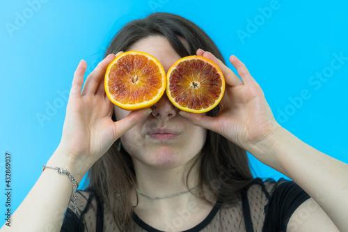 Valokuva Una giovane e bella ragazza si diverte usando un arancia rossa tagliata a metà c