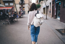 Anonymous Brunette Walking Along Street With Backpack
