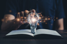 Glowing Light Bulb And Book Or Text Book With Futuristic Icon. Self Learning Or Education Knowledge And Business Studying Concept. Idea Of Learning Online Class Or E-learning At Home.