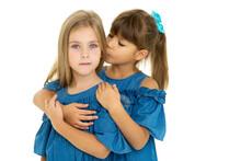 Portrait Of Cute Girl Kissing Her Sister On Cheek