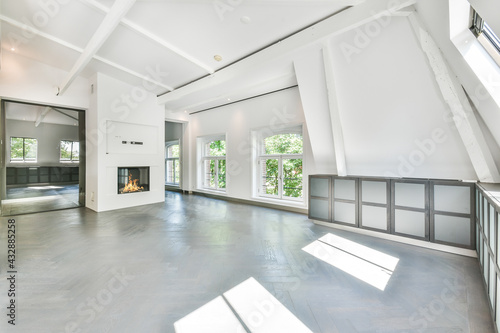 Fotografia Interior of spacious empty room with white walls and parquet floor in contempora