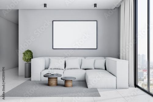 Fototapeta White poster with copyspace in black frame on light grey wall above big sofa in stylish spacious living room with plant in flower pot, coffee tables and city view from big window.  obraz