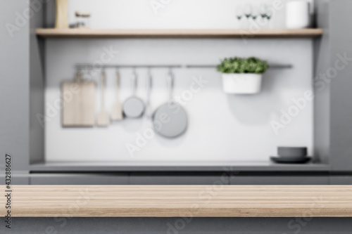 Modern light wooden tabletop with copyspace for your text at blurry kitchen utensils and dishes on grey wall background. 3D rendering, mock up