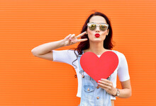 Beautiful Smiling Woman Holding A Red Heart Over Orange Background. Fashion Portrait Stylish Pretty Woman In Sunglasses Outdoor.