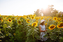 Beautiful  Woman Posing In A Field Of Sunflowers In A Dress And Hat. Young Woman Walks Through A Field Of Sunflowers. Fashion, Lifestyle, Travel And Vacations Concept.