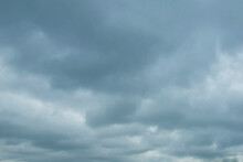The Sky With Dense Cumulus Clouds Is Dark Blue And Gray With A Texture For The Background