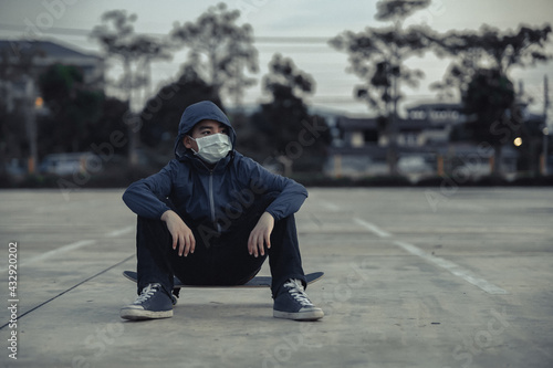 Fototapeta Tired Asian Kid Wearing Protective Face Masks Sitting Outdoors with Skateboard, Skateboarders on Street Keeping Social Distancing While Coronavirus Epidemic., Keep to Healthy Lifestyle. obraz