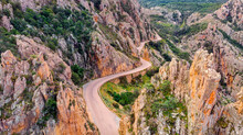 The Calanches De Piana, Drone View Of The Road Between The Mountains. The Calanches De Piana Are A Geological Formation Of Red Porphyry Of Volcanic Origin With Magmatic Rocks.