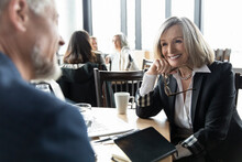 Smiling Businesswoman Meeting With Colleague In Restaurant