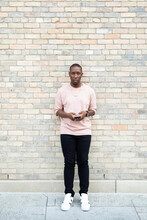 Portrait Confident Young Man Using Smart Phone At Brick Wall