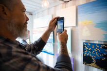 Man With Smart Phone Photographing Paintings Hanging At Bazaar Marketp