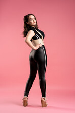 Sexy Plus Size Model With Large Breasts And Toned Buttocks In Black Wear On Pink Background