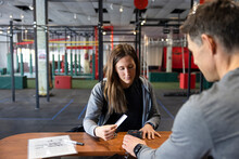 Woman Paying For Gym Membership At Front Desk