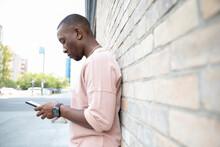 Young Man Texting With Smart Phone Along Urban Brick Wall
