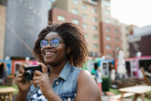 Happy, Carefree Young Woman Using Digital Camera At Urban Bazaar Marke
