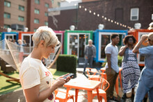 Woman Using Smart Phone At Urban Bazaar Marketplace