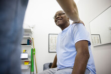 Physiotherapist Comforting Smiling Senior Male Patient In Clinic