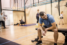 Man Taking A Break From Workout On Bench In Gym
