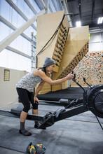Female Climber Programming Rowing Machine In Climbing Gym