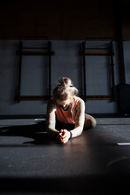 Woman In Face Mask Stretching In Pigeon Pose On Gym Floor
