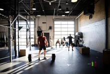 Man Weightlifting With Barbell In Sunny Cross Training Gym