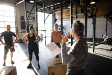 Group Fitness Instructor Leading Class In Sunny Cross Training Gym