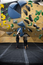 Young Male Climbers Sequencing Below Wall In Climbing Gym