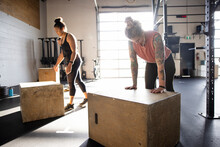 Tired Woman Resting At Box In Cross Training Fitness Class