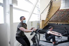 Young Men In Face Masks Using Cardio Equipment In Climbing Gym