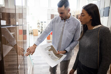 Couple Choosing Color Of Cabinet In Kitchen Showroom