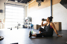 Young Woman Taking Break From Workout Drinking Water On Gym Floor