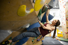 Young Female Climber On Wall In Climbing Gym