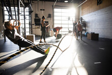 People Doing Cross Training Exercises In Sunny Gym