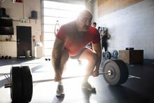 Strong Man Preparing Barbell Deadlift In Sunny Cross Training Gym