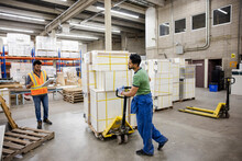 Workers Moving Cargo In Distribution Warehouse