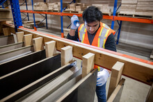 Worker Checking Wooden Panels In Distribution Warehouse
