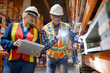 Colleagues Inspecting Building Materials In Distribution Warehouse