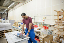 Worker Using Laptop In Distribution Warehouse
