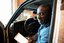Driver Using Digital Tablet Inside Truck