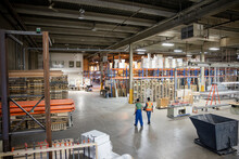 Rear View Of Workers Walking Together In Distribution Warehouse
