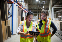 Workers Discussing Work In Distribution Warehouse