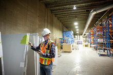 Supervisor Inspecting Building Materials In Distribution Warehouse